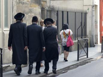 Judeus ortodoxos caminham pelas ruas de Paris.